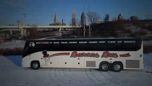 Barons Bus parked in snow against city skyline